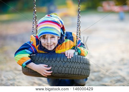 funny little kid boy having fun with chain swing on outdoor playground. child swinging on warm sunny spring or autumn day. Active leisure with kids. Boy wearing colorful clothes