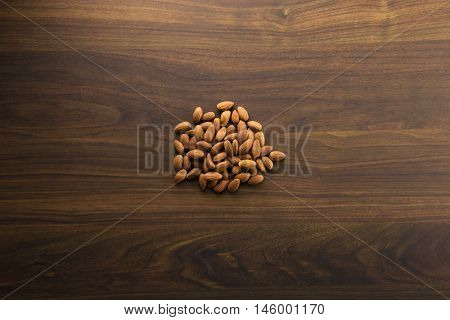 Salt free and oil free almonds on a dark colored table, with plenty of copy space. Intentionally shot in half shadow.