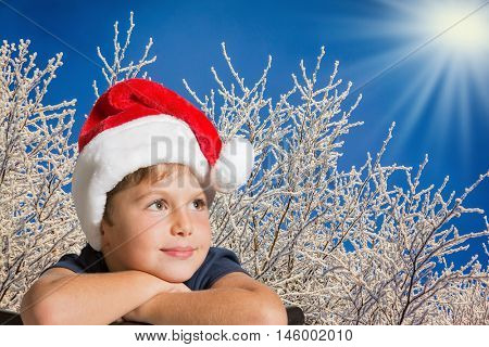 The charming seven-year-old boy in red Santa Claus's cap thoughtfully looks up. The boy is photographed against the snow-covered Christmas forest