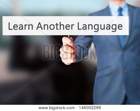 Learn Another Language - Businessman Hand Holding Sign