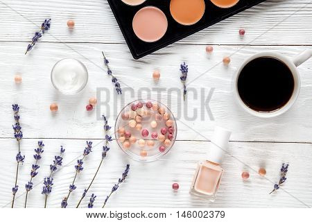 makeup set in beige tones on white table coffe cup top view