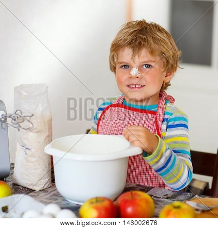 Lovely funny blond little kid boy baking apple cake and muffins in domestic kitchen. Happy child having fun with working with mixer, flour, eggs and fruits at home.