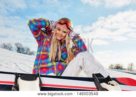 Young female snowboarder sitting on slope