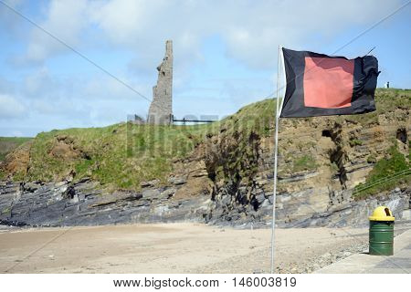 blank flag flying beside surf school with ballybunion castle in background