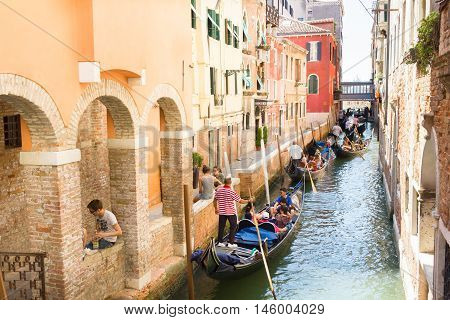VENICE, ITALY- AUGUST 3, 2016: Tourists enjoying the gondolas in the canals near the Bridge of Sighs. The gondolas are the most popular and romantic transportation in the city.