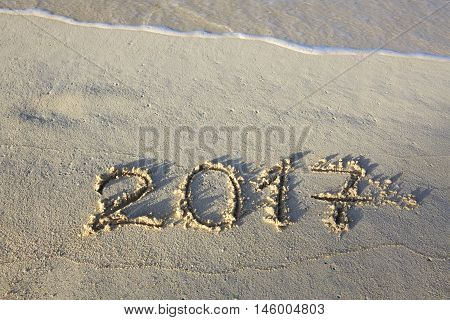 2017 inscription written in the wet beach sand with sea water wave.
