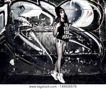 Pretty young woman near graffiti wall, black and white
