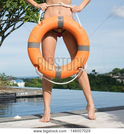 woman wearing bikini at the swimming pool holding ring buoy lifebuoy and glasses