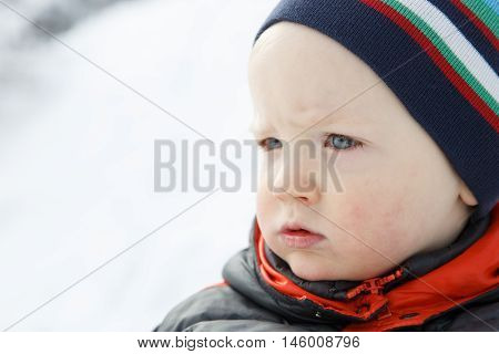 Blue eyed little boy in a winter landscape dressed in warm clothes in thought and observing nature. Active family lifestyle outdoor and natural childhood looking into the future concept.