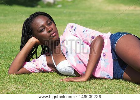 Portrait of a gorgeous african woman with braids and summer clothing lying on a patch of grass looking at the camera