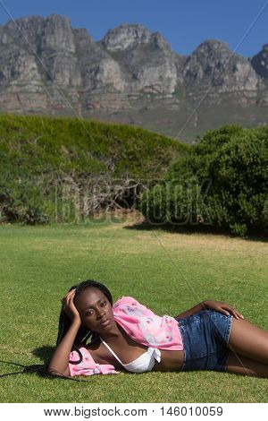 A gorgeous african female in summer style clothing lying in a field with the mountain behind her