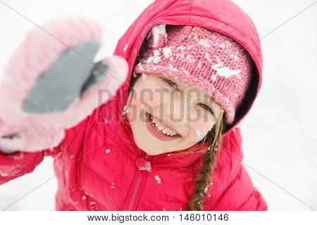 Playful girl with braids enjoying winter and snow dressed in warm clothes playing and catching some sun. Active family lifestyle outdoor and natural childhood carefree childhood concept.