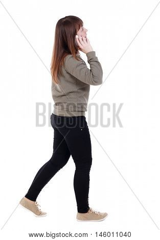 side view of a woman walking with a mobile phone. back view of girl in motion. A girl in a gray jacket talking on the white smartphone and looking up.