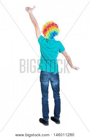 back view of dancing young beautiful man in clown wig. Curly man in a turquoise sweater and clown wig standing hands up.