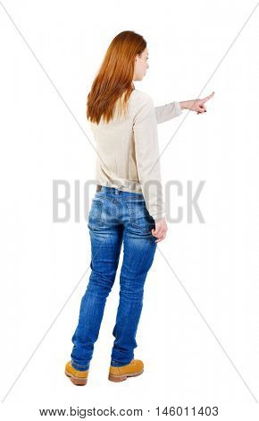 Back view of pointing woman. beautiful girl. girl in a white warm sweater showing with his right hand to the left.