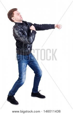 back view of guy funny fights waving his arms and legs. Curly guy in a black leather jacket clumsily fighting.