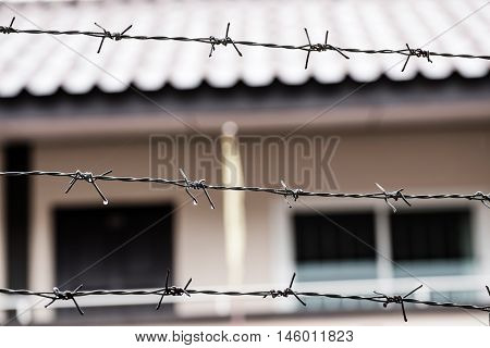 Barbed wire fence with rain drops attached around prison walls, selective focus shallow depth of field