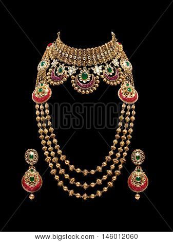 Close up of a complete set of Gold and Diamond necklace with beautiful diamond earrings. Isolated on black background.