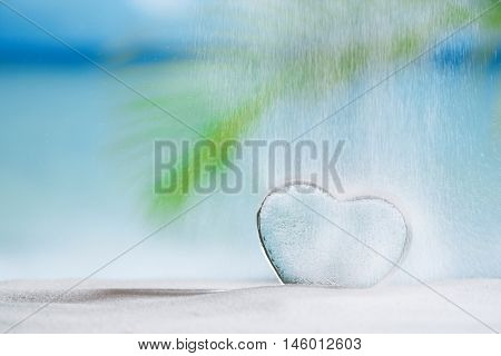 clear glass heart and pouring sand on white sand beach, ocean,  sky and seascape