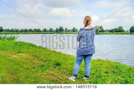 Woman with a long hair braid and decorated a blue shirt stares over the water of a small lake. It's a sunny day in the summer season.