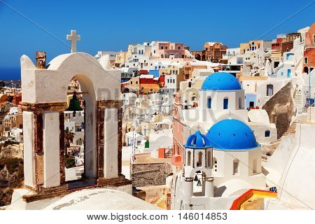 Landscape of Oia town in Santorini Greece with blue dome churches and cross on foreground. Vertical shot