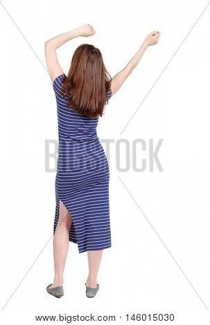 back view of dancing young beautiful woman. brunette in a blue striped dress waving his arms above his head.
