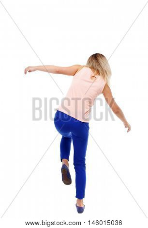 Balancing young woman. or dodge falling woman. Isolated over white background. The blonde in a pink shirt standing on one leg.