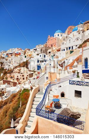 Oia town in Santorini Greece with blue dome churches on foreground. Vertical shot