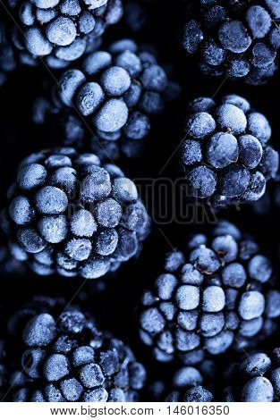 Close up view on frozen Blackberry fruits, on a black stone table. Food background. Dark photo style.