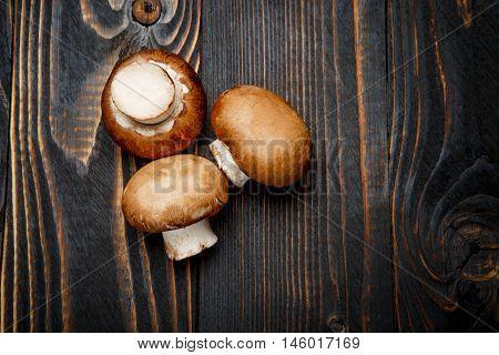 fresh champignon mushroom on wooden background or table