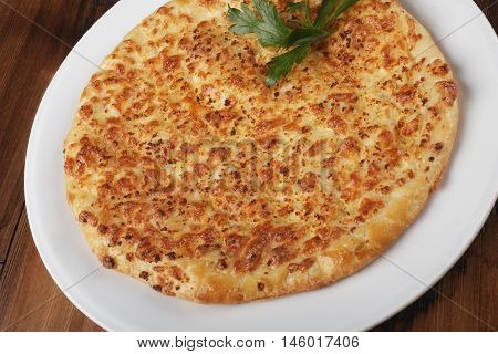 Khachapuri - traditional georgian pie with potatoes and cheese. Cake on a white plate. Wooden background