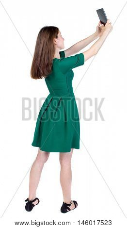 back view of standing young beautiful woman using a mobile phone. slender brunette in a green short dress takes on a tablet PC at the top of something.