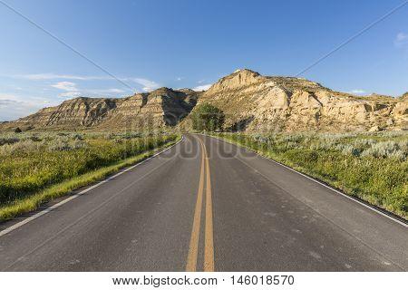 A road traveling through a badlands landscape during summer.