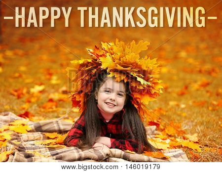 Happy Thanksgiving Day. Happy young girl in yellow autumn wreath lying on plaid in park