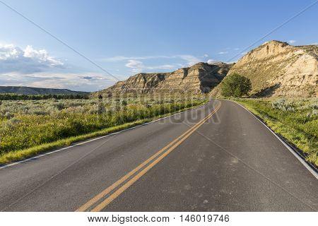 A road traveling through a badlands landscape.