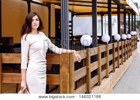 The girl in the bright, simple dress at the entrance to the restaurant