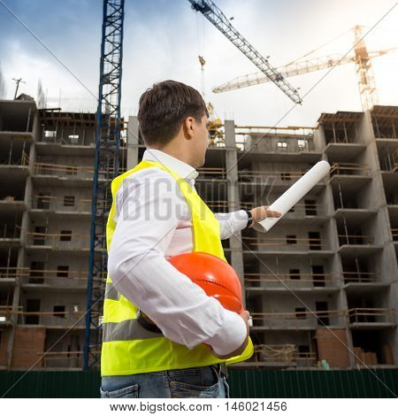 Rear view image of young engineer pointing at building with rolled blueprints
