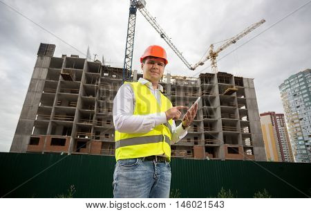 Portrait of building inspector with digital tablet on construction site