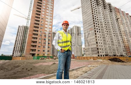 Image of young engineer in hardhat and safety vest posing against buildings under construction