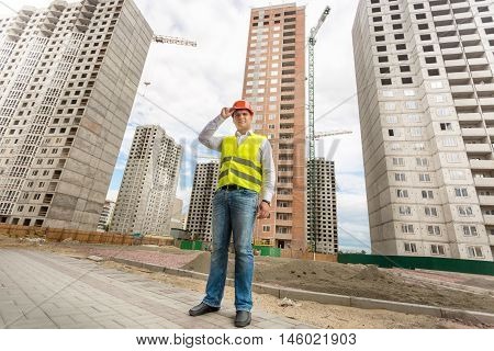 Young businessman in hardhat and safety vest standing on building site