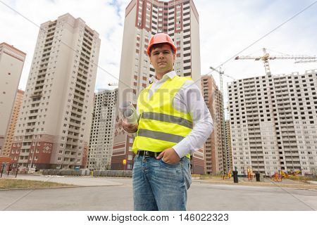 Portrait of construction inspector standing on building site and looking at camera