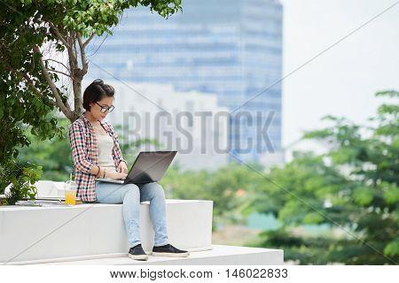 Asian yuong woman with laptop enjoying working outdoors