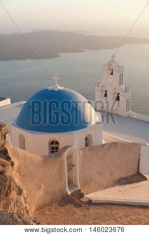 Famous church in Fira Santorini at sunset with a perfect view of the volcano. Vertical shot