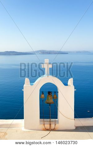 Church bell in Oia Santorini Greece. Sea and volcano on background. Vertical view