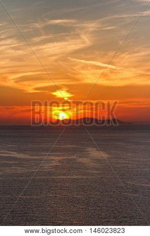 Sunset in Oia Santorini. Sun behind the volcano. Vertical shot