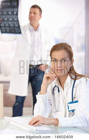 Young attractive female doctor working on computer sitting at desk in office, smiling, male doctor in background studying x-ray image.?