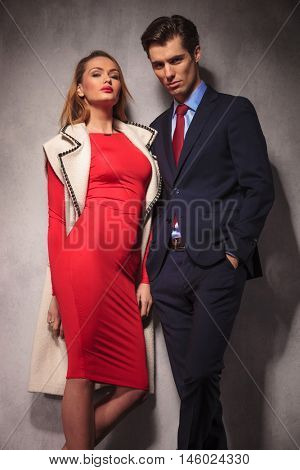 elegant couple standing together in studio, woman wearing a red dress and a long wool coat and man in suit and tie