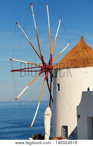 Windmill in Oia Santorini. Shot at sunrise. Vertical shot. The sea on background