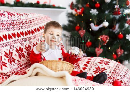 Little Baby Boy in Santa suit with Christmas decorations. New Year and Christmas concept