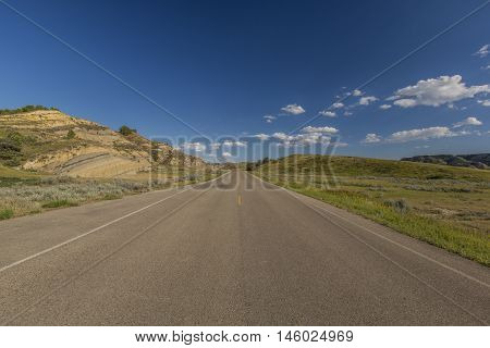 A road traveling through badlands during summer.